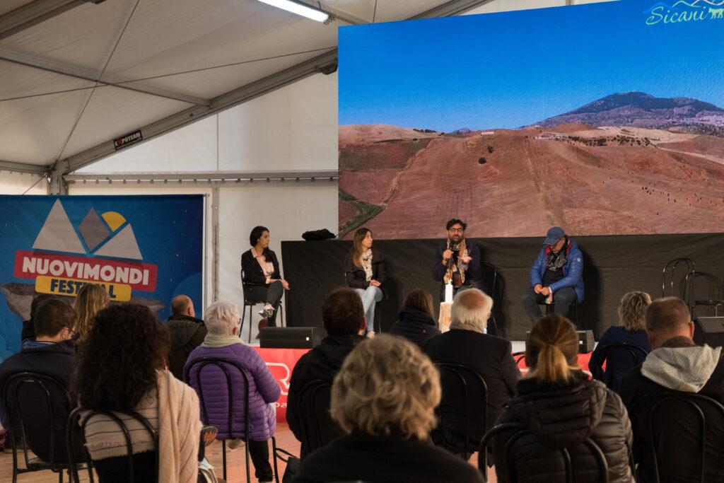 """Un momento di  """"Muovere le Montagne"""" al Nuovi Mondi Festival (proiettata sul palco si vede una foto della zona dei Monti Sicani)"""